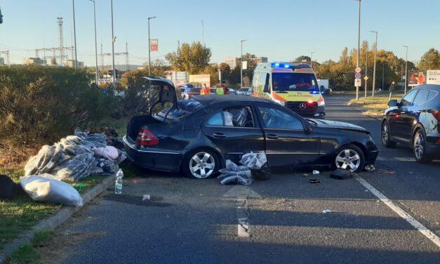Csúnya baleset a 11. kerületben – Átszáguldott a Mercedes a piroson, egy Nissan Micraval ütközött, majd felugratott a járdaszegélyre és egy jelzőlámpát is kidöntött – Fotók
